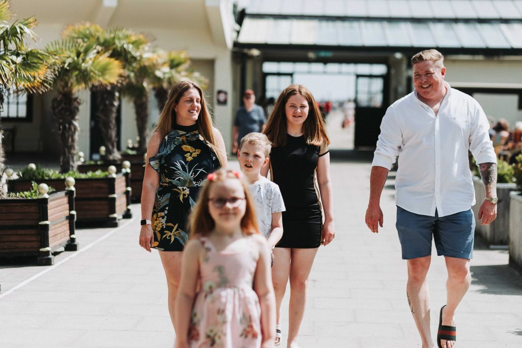 family walking towards camera smiling