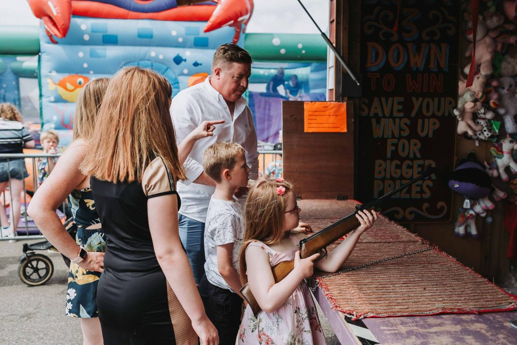 family at shooting gallery on herne bay pier with youngest daughter holding a gun