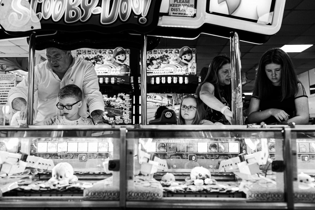 family playing together on penny arcades in amusements
