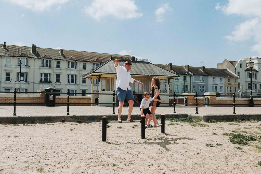 dad and kids balancing on play equipment on beach