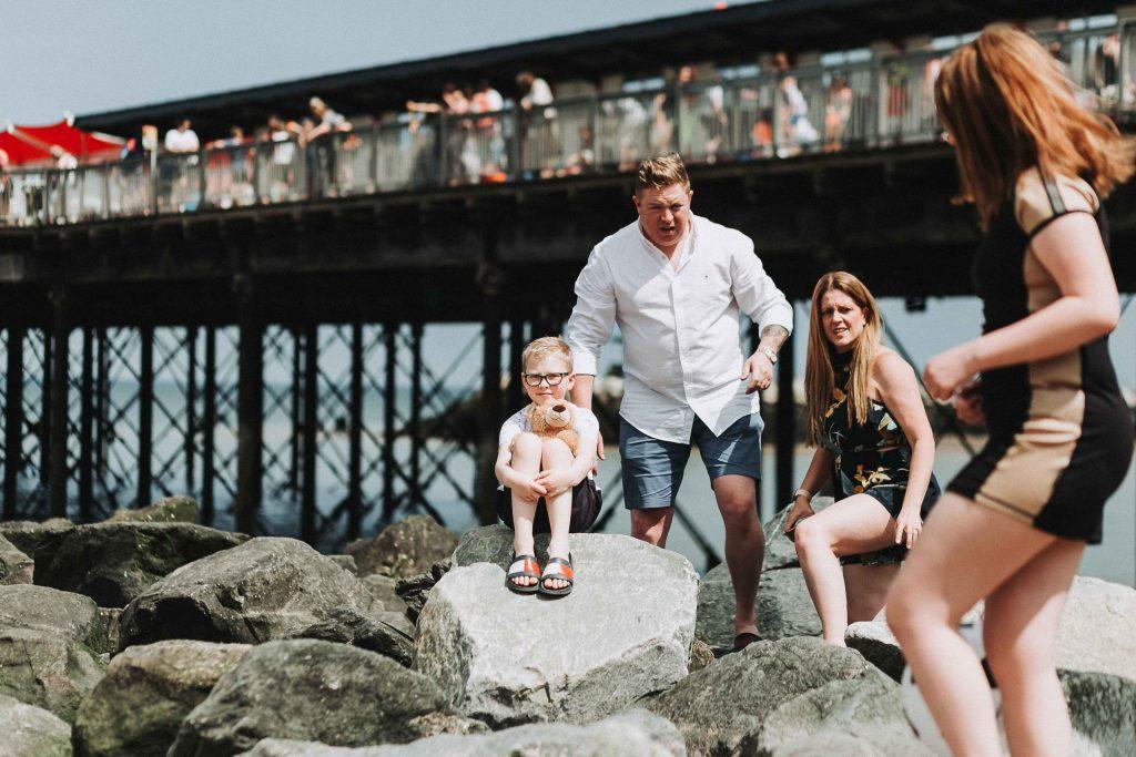boy posing with teddy bear on rocks on herne bay beach with family around him